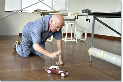 Father Maur van Doorslaer catches one of his highly detailed model cars before it gets away from him on the floor of his art studio at the St. Andrew's Abbey in Valyermo.