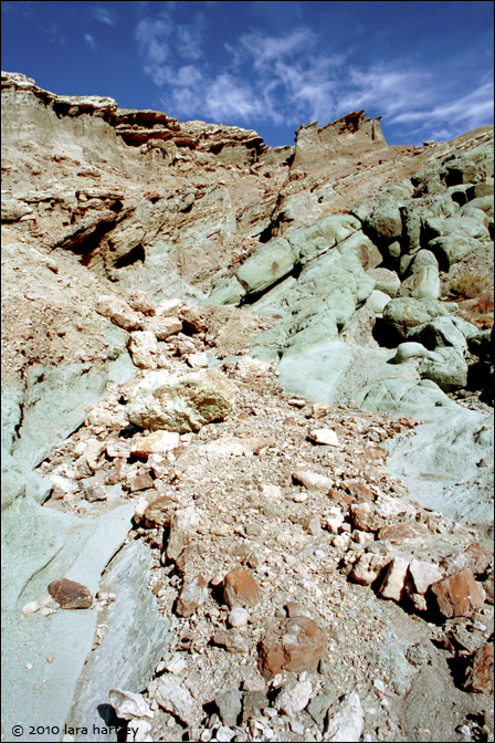 A myriad of rocks includes volcanics (red rhyolite breccia and white tuff) to shale to feldspar and quartz fragments to bright green clay.