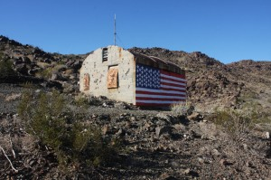 The old cabin with a flag painted on the side.