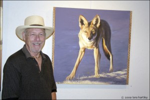 Artist Chuck Caplinger poses beside his painting of a young coyote.