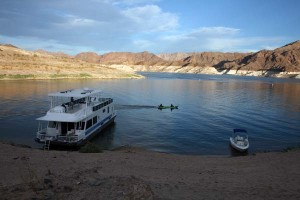 Housboat and motor boat on sandy beach at Lake Mead.