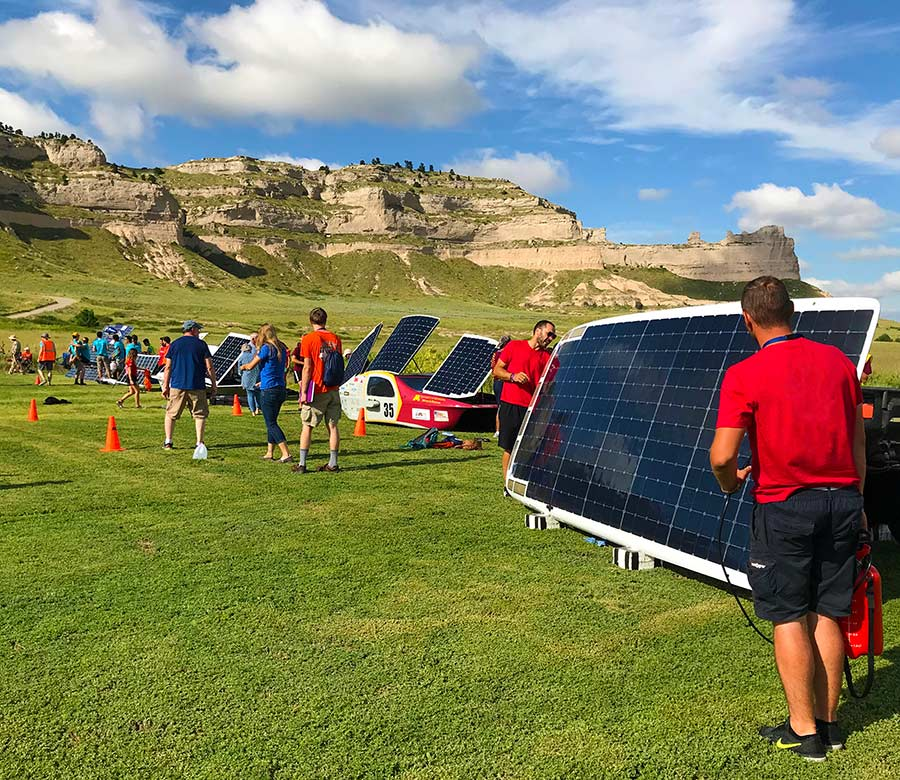 Solar cars propped up for charging on short grass with people milling about and working on the cars. A large bluff and blue skies dotted with clouds are in the background. Solar cars charging during the 2018 American Solar Challenge at Scotts Bluff National Monument. NPS Photo