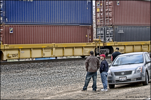 Rail fans watch a container train roll by near a crossing in Caliente, Calif.
