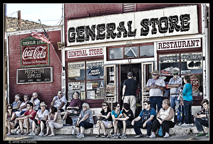 Visitors to Old West Days sat in the shade in front of the General Store enjoying the fun going on in the street.