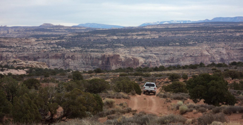 Scrub-brush landscape with dirt road and ranger vehicle ORV use in scenic Glen Canyon National Recreation Area NPS