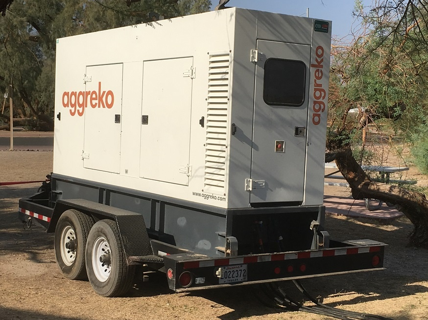 A white trailer-mounted generator is hooked by thick cables to an electrical panel behind Furnace Creek Visitor Center. Southern California Edison is providing this generator to power Furnace Creek Visitor Center until the underground cable is replaced. NPS photo