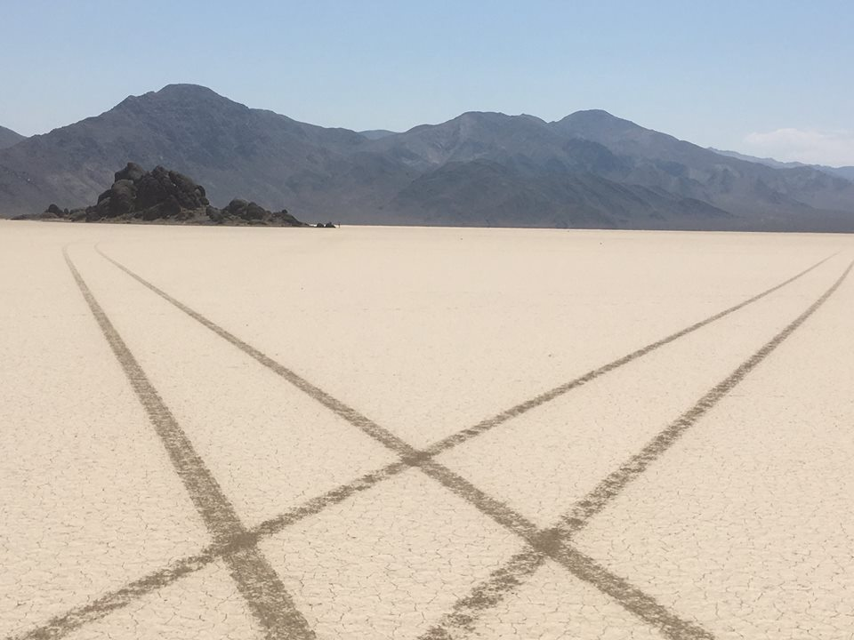 Vehicle tracks on the north end of Racetrack Playa. The Grandstand is the rock formation visible in the background. NPS Photo