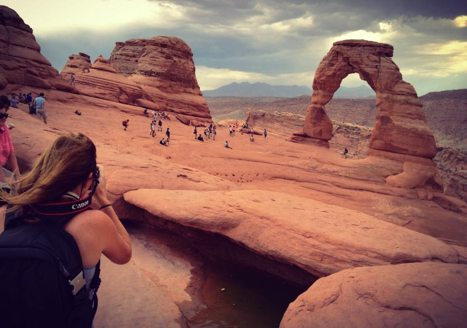 Delicate Arch in the distance  and the natural amphitheater. Author in the foreground photographing the Arch.  Photo by Abbie Archer.