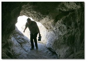 Videographer, Jim Bremner, as he follows author into one of the mud caves.