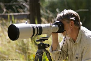 Wildlife photographer Ron Wolf aims his big Canon lens at the hummingbird feeding station during the recent photography workshop. Visit Ron's Flickr stream for some great images. www.flickr.com/photos/rwolf/