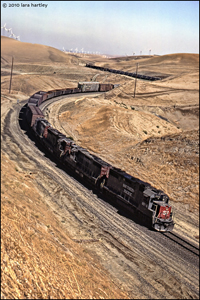 "Caption: In 1986, a Southern Pacific train eases down a long ""Ess"" curve on the now abandoned right-of-way over Central California's Altamont Pass. Union Pacific bought the historic SP several years ago and it is now one of the many ""fallen flags""  in railroad history. The Altamont Pass Wind Farm, seen in the background, is a one of the earliest wind farms in the United States."