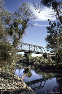 This rail bridge provides an unusual backdrop for photographing a train as it crosses the Stanislaus River at Riverbank, Calif. Unfortunately, one did not show up while I was waiting — and waiting.