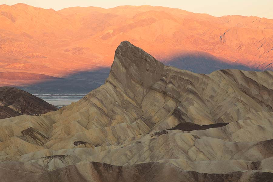 badlands with a prominent hill and sunrise light turning distant mountains pink Manly Beacon from Zabriskie Point at sunrise. NPS / E. Hoerner