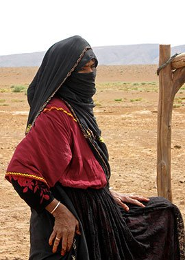 Saharan woman, traditionally dressed, at communal well.